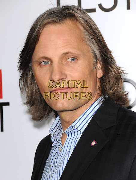 """VIGGO MORTENSEN .arriving at AFI Fest's Gala Screening of """"The Road"""" at Grauman's Chinese Theatre in Hollywood, California.  November 4th 2009..portrait headshot pin brooch badge  black pinstripe blue striped shirt .CAP/RKE/DVS.©DVS/RockinExposures/Capital Pictures."""