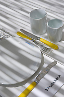 Detail of a place setting on the terrace table with yellow cutlery and white crockery with the name of the island printed on it