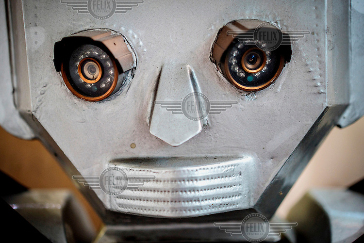 The 'head' and 'eyes' of one of the humanoid traffic robots made at the Women's Tech workshop in Kinshasa. The eyes consist of small cameras and the head is made out of bonded plates of aluminium. <br /> Women's Tech, a small enterprise started by Therese Kirongozi, a local entrepreneur, manufactures humanoid traffic robots that are intended to blend the functions of traffic lights with human traffic police officers to control and monitor traffic flow. They are solar powered, equipped with green and red lights and can play pre-recorded messages to pedestrians to let them know when it's safe to cross the street. They also have in-built video cameras which convey footage back to a central office where it is evaluated and used to enhance traffic flow in the city.