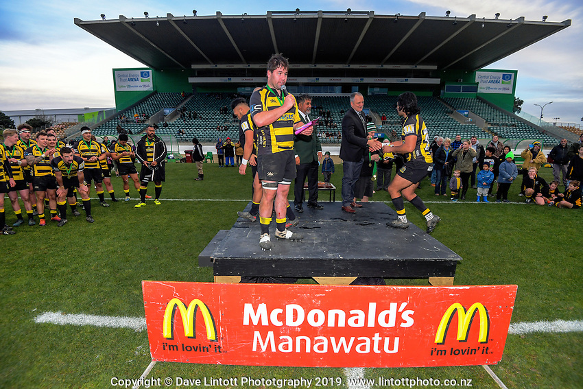 Yellows players are given their winners' medals as captain Hayden Stratford calls the team up after the 2019 Manawatu premier club rugby Hankins Sheild final match between Varsity and Feilding Yellows at CET Arena in Palmerston North, New Zealand on Saturday, 13 July 2019. Photo: Dave Lintott / lintottphoto.co.nz