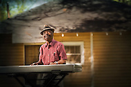 An older african-american blues musician has a smoke while playing his keyboard out behind his home.