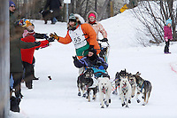 Spectators cheer on Kelly Maixner on the bike trail near the Native Hospital in mid-town Anchorage during the ceremonial start of the 2011 Iditarod