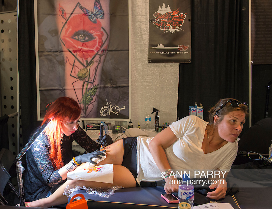 Garden City, New York, USA. September 13, 2015. DANIELLE FOGERTY, of Cutchogue, leans on her side as KAMOMILLA SNAIL, a tattoo artist from Italy, tattoos her at the United Ink Flight 915 Tattoo convention at the Cradle of Aviation Museum in Long Island. Snail tattooed a delicate intricate orange tiger lily flower on Fogerty's thigh.