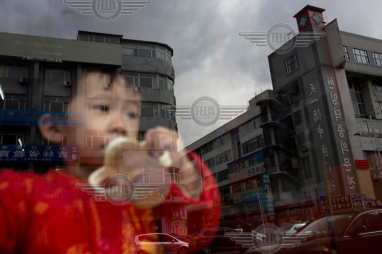 A child, reflected in a window pane, drinks from a bottle as he looks out on to a street. The buildings outside sport signage in both Korean & Chinese scripts. /Felix Features