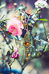 Photograph of a vintage key pendant among wild pink roses