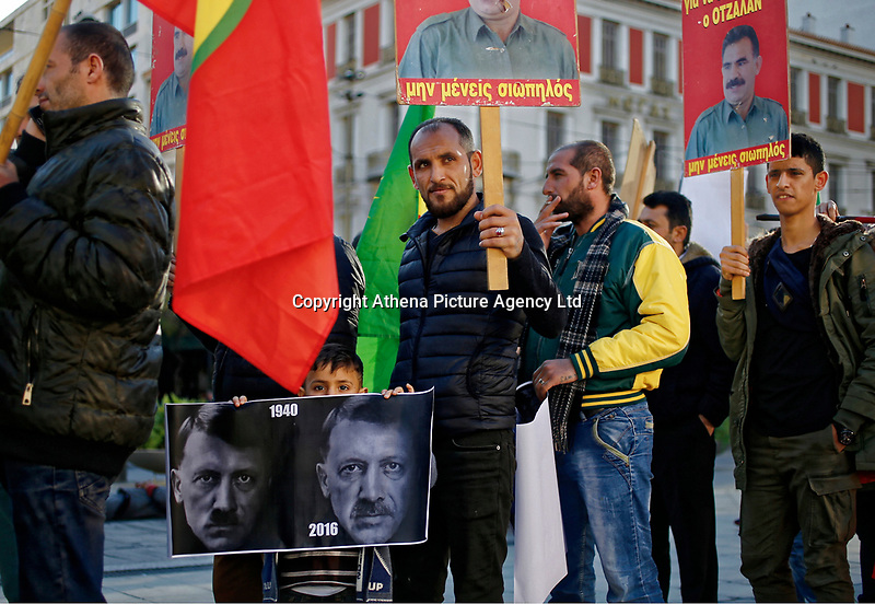 """Pictured: A young boy joins adult Kurdish protesters with a """"Dictator Erdogan"""" banner gather at Syntagma Square in Athens Greece. <br /> Re: Kurdish people with protest against the Turkey president  Recep Tayyip Erdogan's visit to Greece. Thursday 07 December 2017"""