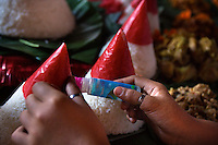 A student at Kartini Emergency School applies the finishing touches to traditional rice cones by gluing red oil paper on to the top of the rice cones, part of the Indonesian Independence Day celebrations at the school in North Jakarta. Acquiring practical skills is an important part of the education programme. Since the early 1990s, twin sisters Sri Rosyati (known as Rossy) and Sri Irianingsih (known as Rian) have used their family inheritance to set up and run 64 schools in different parts of Indonesia, providing primary education combined with practical skills to some of the country's most deprived children.