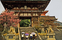 Japan.  Kiyomizu Temple, Kyoto.  People with umbrellas climbing the steps towards the main gateway in characteristic drizzle.