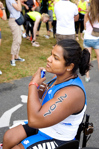 Minda sprays on body glide while preparing to compete in the Aquaphor New York City Triathlon in New York on July 8, 2012.