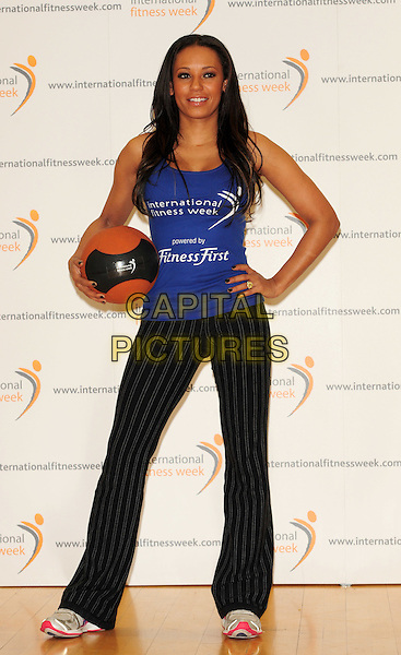 MELANIE BROWN aka MEL B .Launches The International Fitness Week, Fitness First Gym, Tottenham Court Road, London, England..January 28th, 2010.photocall full length medicine ball blue black pinstripe striped trousers trainers top tattoo basket holding vest exercise nail varnish polish scary spice .CAP/CJ.©Chris Joseph/Capital Pictures.