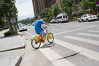 A man rides a bikeshare bicycle at a crosswalk in Xian, Shaanxi, China.