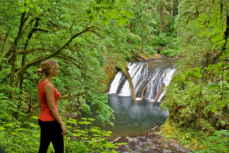 Young woman hiking at Silver Falls State Park at Lower North Falls. Oregon