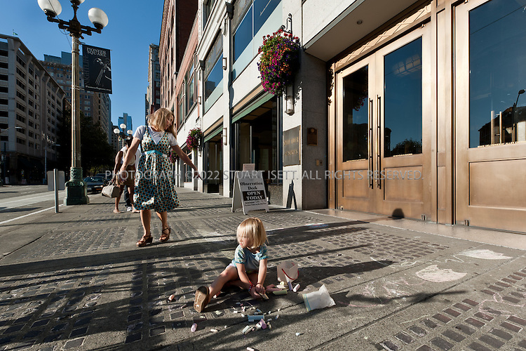 9/27/2010--Seattle,WA, USA..Petra Franklin and her daughter Naomi, 3, do chalk drawings on the sidewalk outside the Smith Tower in Seattle, WASH., where the family lives in the penthouse apartment...Smith Tower, located in Seattle's Pioneer Square neighborhood, is the oldest skyscraper in the city. Completed in 1914 it has 38 floors and  remained the tallest building on the West Coast until the Seattle Space Needle overtook it in 1962. The tower is 462 ft (143 meters) from street level to the top of the pyramid with a small glass lighthouse at the top...Petra Franklin and her husband David Lahaie live in the pyramid on top of Smith Tower with their two daughters Simone, 6, and Naomi, 3. Franklin is co-founder and general partner of Vault Capital, a venture capital fund with offices in Smith Tower...Copyright © 2010 Stuart Isett. All rights reserved.