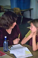 Teacher helping student with writing project. Oregon.