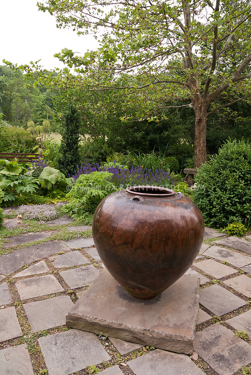 Stone patio, large garden pot ornament, evergreens, Buxus boxwood, Veronica or salvia, thymus thyme herbs in bloom, focal point