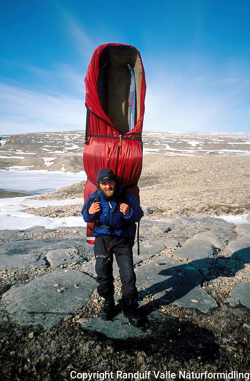 Mann bærer stor ekspedisjonspulk på ryggen. ---- Man carrying large expedition sled on his back.