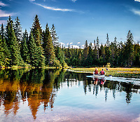 A canoe disturbs forest reflections on a shallow estuary in Algonquin Park, Ontario, Canada