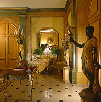 A pair of carved wooden torcheres flanks a doorway in the entrance hall which is filled with elaborate carved and gilded furniture including a Louis XV bureau plat