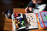 My older son, almost four, arranges Matchbox cars on the coffee table while his brother, almost one, crawls on the floor with blocks.