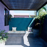 Walls painted deep turquoise and lilac result in a calm and tranquil outdoor space