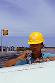 Redencao, Brazil. Man in bright yellow hard hat filling a light aeroplane with fuel; Shell sign in background.
