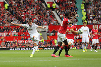 Pictured L-R: Gylfi Sigurdsson of Swansea and Tyler Blackett of Manchester United.  Saturday 16 August 2014<br /> Re: Premier League Manchester United v Swansea City FC at the Old Trafford, Manchester, UK.