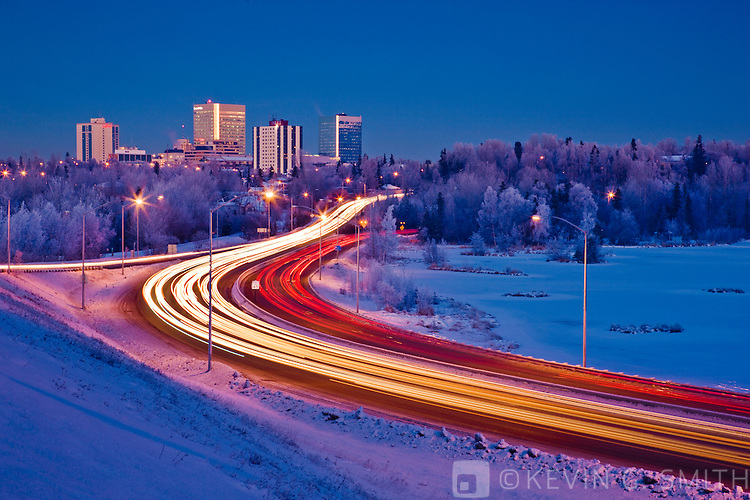 Photo of the Anchorage skyline at twilight, traffic traveling along Minnesota blvd. next to Westchester Lagoon, winter, Anchorage, Southcentral Alaska, USA.
