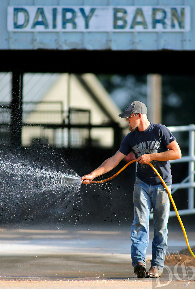 NWA Media/DAVID GOTTSCHALK - 8/21/14 - Nathan Ramey, with the Washington County Fairgrounds, washes off the new concrete entry to the Dairy Barn on the grounds in Fayetteville Thursday August 21, 2014. The 2014 Washington County Fair runs from Tuesday August 26  through Saturday August 30 featuring rides, exhibitions and vendors.