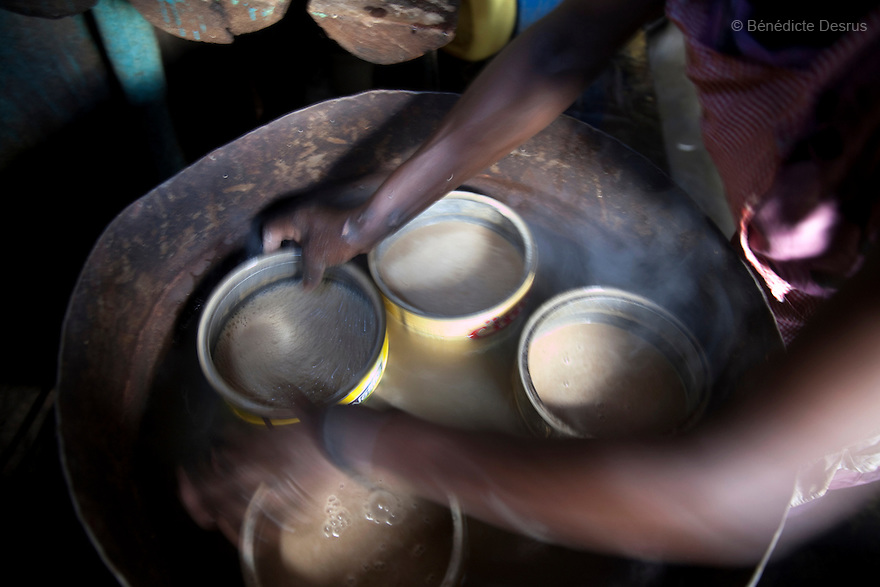 Busaa, a traditional fermented beer, is being warmed at the Madiaba Busaa club at midday in a Nairobi slum on April 14, 2013. Busaa is made by crudely fermenting maize, millet, sorghum or molasses. At Kshs 35 per liter it is much cheaper than a Kshs120 half-liter bottle of commercial beer. The local brew was legalised in 2010 and since then Busaa clubs have become increasingly popular in slums and rural areas. Drinking is on the rise in Kenya, especially among young people. Photo by Benedicte Desrus