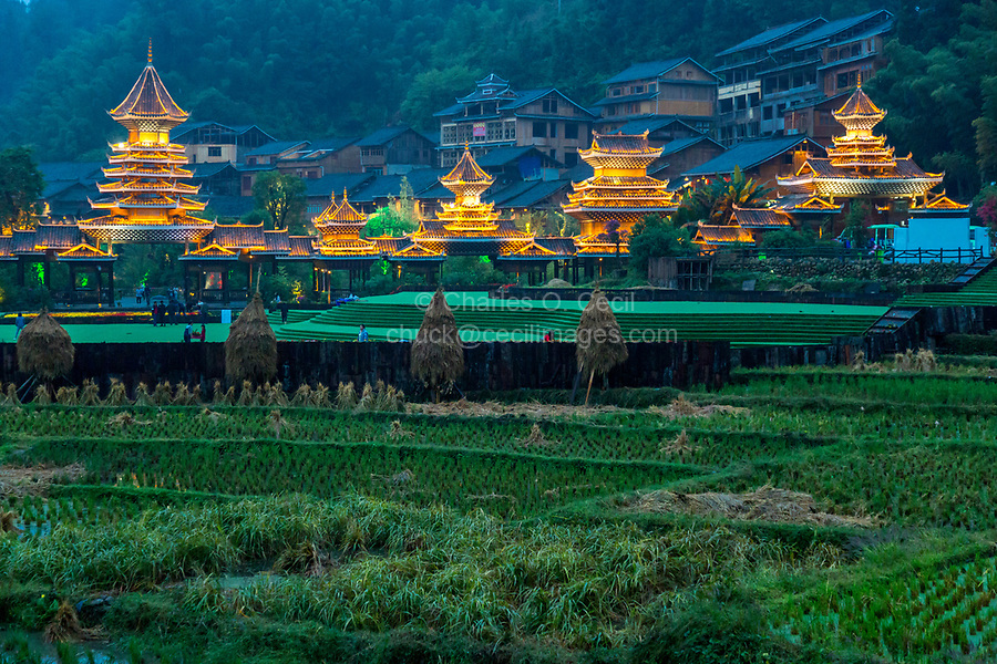 Zhaoxing, Guizhou, China, a Dong Minority Village.  In early evening buildings around the entrance to the village are illuminated.  Rice paddies in foreground.