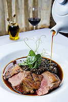 Ripasso duck jus is poured over Anatra Alla Lenticchia, a seared duck breast with lentils, pancetta, duck confit and pea vines at La Dolce Vita in Seattle. (Photo by Andy Rogers)