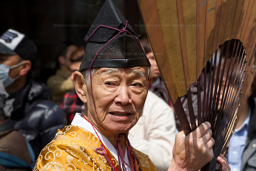 A priest with a large gold fan during the Kanamara matsuri or festival of the Steel phallus Kawasaki Daishi, Kawasaki, Kanagawa, Japan. Sunday, April 2nd 2017. The Kanamara Penis festival takes place on the first Sunday of April and celebrates the local legend of a penis eating demon who was defeated after being tricked into biting a steel phallus. The festival is popular with Japan's gay community and now uses its notoriety to raise money for HIV and AIDS charities. It is also wildly popular with foreign and Japanese.tourists.