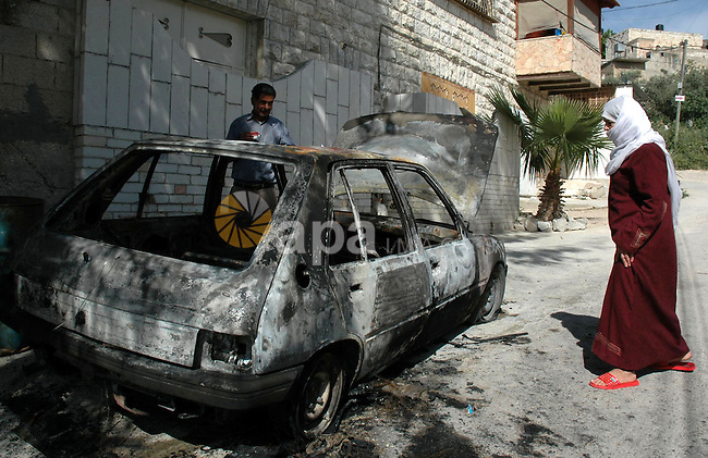 """Palestinians inspect the car that was allegedly set on fire by Jewish settlers in the village of Hawara, near the West Bank city of Nablus, on April 14, 2010. Israeli settlers desecrated a mosque and set fire to two cars in the occupied West Bank, Palestinian security officials said. The Israeli army confirmed that """"anonymous suspects"""" scrawled graffiti, including a Jewish star of David alongside the name of the Prophet Mohammed written in Hebrew.  Photo by Nedal Shtieh"""