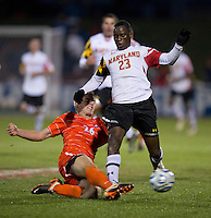 Kyle Fisher (26) of Clemson tackles the ball away from Schillo Tshuma (23) of Maryland during the game at the Maryland SoccerPlex in Germantown, MD. Maryland defeated Clemson, 1-0, in overtime.  With the win the Terrapins advanced to the finals of the ACC men's soccer tournament.