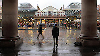 Covent Garden Market seen from the Royal Opera House, London, UK. The man seen from behind, with black suit and top hat is probably an old street artist waiting for the rain to stop. Picture by Manuel Cohen