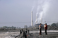 A young family stand in an empty lot near smoke stacks of a cement factory on the outskirts of  Datong, Shanxi Province, China..04 Jul 2005