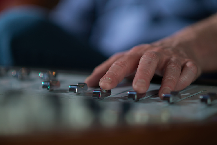 Eddie Ashworth operates makes adjustments to the mixing board during a recording session at MDIA Sound.