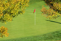 The red flag on the pin stands out on the green in the fall