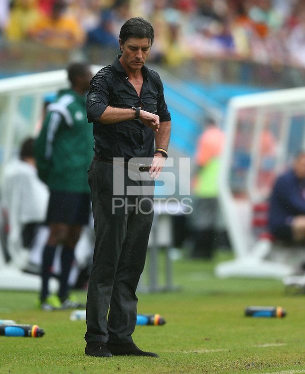 A soaking wet Germany coach Joachim Loew checks his watch