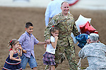 Nevada Army National Guard Chief Warrant Officer Glen Spadin walks off the arena floor with his children, from left, Sarah, 4, Mark, 9, and Rachel, 7, after his surprise return from Afghanistan during Patriot Night at the Reno Rodeo in Reno, Nev. on Friday, June 19, 2015. Spadin returned after a year in Afghanistan to surprise his six children.  <br /> Photo by Cathleen Allison