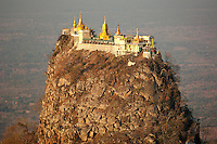 The Mount Popa Temple in Myanmar, a complex of monasteries, stupas and shrines on top of an impressive rocky volcanic plug reached by 770 steps, shines golden bright shortly after sunrise.