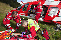 "Switzerland. Canton Ticino. Blenio valley. A Rega Agusta AW109 SP Grand ""Da Vinci"" helicopter on pastures above Olivone. The emergency physician, Doctor Damiano Salmina, takes care of a badly injured man lying in a stretcher. The patient is a worker from the Rotex company who was injured during a logging operation. The doctor gives the prime cure for a medical treatment. He is helped by the pilot Mario Agustini (L) and the paramedic Giovanni Beldi  (standed up). Intravenous therapy. All Rega helicopters carry a crew of three: a pilot, an emergency physician, and a paramedic who is also trained to assist the pilot for radio communication, navigation, terrain/object avoidance, and winch operations. The name Rega was created by combining letters from the name ""Swiss Air Rescue Guard"" as it was written in German (Schweizerische Rettungsflugwacht), French (Garde Aérienne Suisse de Sauvetage), and Italian (Guardia Aerea Svizzera di Soccorso). Rega is a private, non-profit air rescue service that provides emergency medical assistance in Switzerland. Rega mainly assists with mountain rescues, though it will also operate in other terrains when needed, most notably during life-threatening emergencies. As a non-profit foundation, Rega does not receive financial assistance from any government. People in distress can call for a helicopter rescue directly (phone number 1414). The AgustaWestland AW109 is a lightweight, twin-engine, helicopter built by the Italian manufacturer Leonardo S.p.A. (formerly AgustaWestland, Leonardo-Finmeccanica and Finmeccanica). Leonardo S.p.A is an Italian global high-tech company and one of the key players in aerospace. In close collaboration with the manufacturer, the Da Vinci has been specially designed to cater for Rega's particular requirements as regards carrying out operations in the mountains. It optimally fulfills the high demands made of it in terms of flying characteristics, emergency medical equipment and maintenance. Safety, performance a"