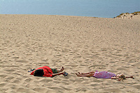 Boy and girl lying on the Great Dune of Pyla, Europe's tallest sand dune, Arcachon Bay, France.