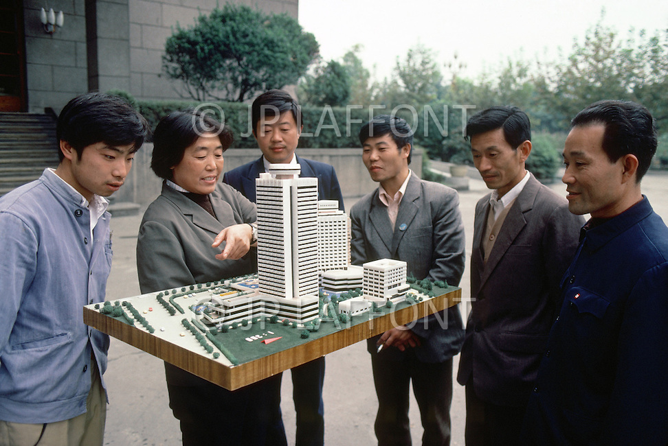 October 1984. At Cheng Du (in Si Chuan province) architects and worksite foremen, examine the model of a hotel scheduled for building.
