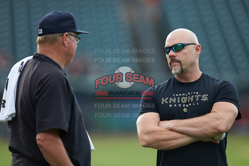 Charlotte Hornets conditioning coach Shawn Powell (right) chats with pitching coach Steve McCatty prior to the game against the Louisville Bats at BB&T BallPark on June 22, 2019 in Charlotte, North Carolina. The Hornets defeated the Bats 7-6. (Brian Westerholt/Four Seam Images)