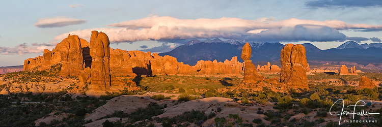 Panoramic view of Balanced Rock in Arches National Park and the La Sal Mountains, Moab, Utah, USA at sunset with clouds.