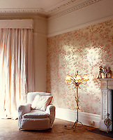 One wall of this Victorian living room is covered in a glossy wallpaper