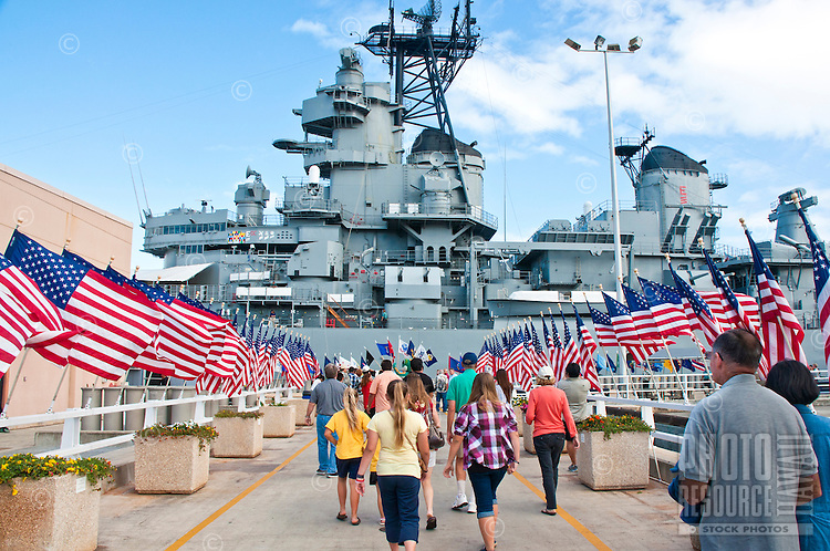 Visitors to the battleship USS Missouri museum walk past rows of American flags, Pearl Harbor, O'ahu.