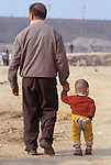 Man and child walking on dusty plain made by razing old town of Fuling; China, Asia; impacted by 3 Gorges Dam; 041703