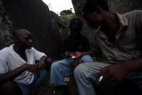 """(from left) thomas, Leroy and Steven divide among each other doses of marijuana  to be sold in Monrovia, Liberia on  Sunday March 18 2007..Melvin, 29 AKA """"Dad"""",  John, 29 AKA """"Desperate Soldier, Thomas 28 AKA """"Bullet Patrol"""", Leroy, 28, AKA """" Pussy Mechanic"""" and Steven 27 AKA """"Field Marshall"""" are all former child soldiers that found each other on the streets after the last round was fired in Liberia. Since then they """"Hustle"""" to put some food in their stomachs and buy some drugs to """" make them forget about their lives""""..ALL NAMES HAVE BEEN FICTIONALIZED TO PROTECT THE IDENTITIES OF THE 5 MEN."""